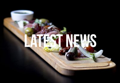 wooden platter of meets and olives and the words latest news
